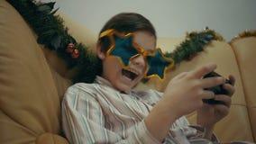 Aantrekkelijk jong jongen het spelen videospelletje of het surfen sociaal netwerk op zijn smartphone stock videobeelden