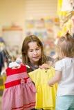 Aantrekkelijk jong mamma die kleding met haar dochter kiezen Stock Foto's