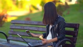 Aantrekkelijk jong meisje die een broodje eten en aan laptop, die aan de telefoon werken spreken stock video