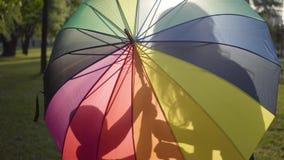 Aantrekkelijk jong meisje die met multi-colored paraplu weinig broer in het park kussen De vrije tijd van de zomer Gelukkige Sibl stock videobeelden