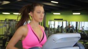 Aantrekkelijk jong meisje die op de tredmolen in de gymnastiek lopen stock video