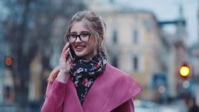 Aantrekkelijk jong meisje die somebody op de telefoon roepen, dan graag sprekend en gelukkig glimlachend Modieus kijk, roze comfo stock video