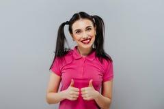 Aantrekkelijk jong meisje met duimen omhoog op grijs royalty-vrije stock foto's