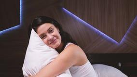 Aantrekkelijk jong meisje thuis Het koesteren van hoofdkussen in haar bed stock footage