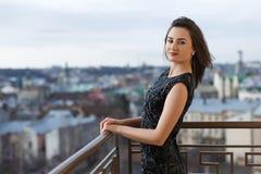 Aantrekkelijk jong mooi meisje die het klassieke zwarte kleding stellen op het balkon van de luxebouw dragen Royalty-vrije Stock Fotografie