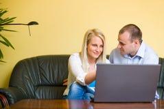 Aantrekkelijk jong paar dat laptop met behulp van. stock fotografie