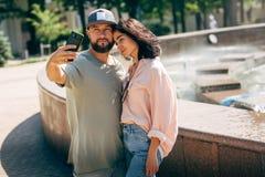 Aantrekkelijk jong paar die selfie in sity centrum doen stock foto's