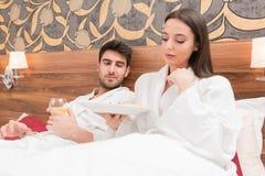 Aantrekkelijk jong paar die in witte robes, van voedsel en drank genieten stock foto
