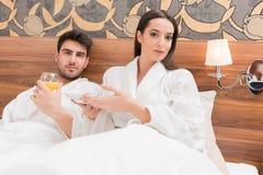Aantrekkelijk jong paar die in witte robes, van voedsel en drank genieten stock afbeelding