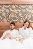 Aantrekkelijk jong paar die in witte robes, van voedsel en drank genieten stock foto's