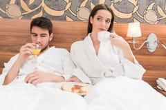 Aantrekkelijk jong paar die in witte robes, van voedsel en drank genieten royalty-vrije stock afbeeldingen