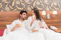 Aantrekkelijk jong paar die in witte robes, van voedsel en drank genieten royalty-vrije stock fotografie