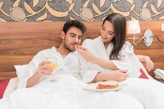 Aantrekkelijk jong paar die in witte robes, van voedsel en drank genieten royalty-vrije stock foto's