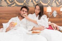 Aantrekkelijk jong paar die in witte robes, van voedsel en drank genieten royalty-vrije stock foto