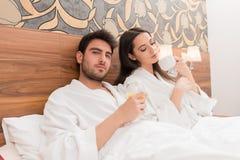 Aantrekkelijk jong paar die in witte robes, van voedsel en drank genieten royalty-vrije stock afbeelding