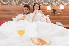 Aantrekkelijk jong paar die in witte robes, van voedsel en drank genieten stock afbeeldingen
