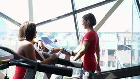 Aantrekkelijk Kaukasisch meisje die op de tredmolen in de sportgymnastiek lopen stock footage