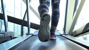Aantrekkelijk Kaukasisch meisje die op de tredmolen in de sportgymnastiek lopen met telefoon en oortelefoons Camera in 4K stock footage