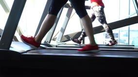 Aantrekkelijk Kaukasisch meisje die op de tredmolen in de sportgymnastiek lopen met telefoon en oortelefoons Camera in 4K stock video