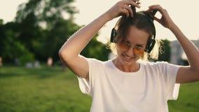 Aantrekkelijk Kaukasisch meisje die pret hebben in openlucht Stellend en glimlachend aan camera die witte T-shirt, hoofdtelefoons stock footage