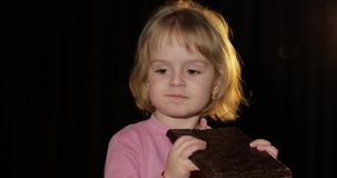 Aantrekkelijk kind die een reusachtig blok van chocolade eten Leuk blonde meisje stock videobeelden