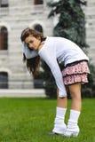 Aantrekkelijk kort rok jong meisje die zich op het tuingras bevinden stock foto's