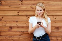 Aantrekkelijk lachend wijfje die zich met mobiele telefoon tegen houten muurachtergrond bevinden royalty-vrije stock fotografie