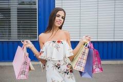 Aantrekkelijk, leuk en glimlachend meisje binnen met kleurrijke het winkelen zakken in haar handen Het onderzoeken van de afstand stock fotografie