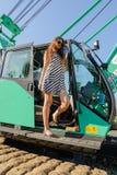 Aantrekkelijk meisje bij de cabine van de bouwkraan Stock Foto's