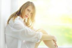 Aantrekkelijk meisje bij het venster Stock Afbeelding