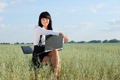 Aantrekkelijk meisje dat aan computer in aard werkt Stock Afbeelding
