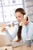 Aantrekkelijk meisje dat aan laptop werkt die op telefoon spreekt Royalty-vrije Stock Foto's