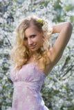 Aantrekkelijk meisje dat zich dichtbij bloeiende boom bevindt Royalty-vrije Stock Afbeeldingen
