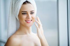 Aantrekkelijk meisje die anti-veroudert room op haar gezicht zetten stock foto's