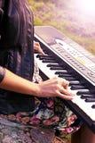 Aantrekkelijk meisje die een synthesizer op aard spelen Een elektrische pianotribunes in aard Stock Foto