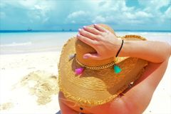 Aantrekkelijk meisje die en op het paradijsstrand zonnebaden ontspannen, die haar kleurrijke strohoed houden royalty-vrije stock afbeelding