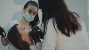 Aantrekkelijk meisje die op tanden liggen die behandeling reinigen 4K stock videobeelden