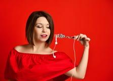Aantrekkelijk meisje die in rode kleding een vork in handen houden op de hoofdtelefoonstop Trof te eten voorbereidingen royalty-vrije stock fotografie