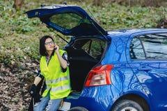 aantrekkelijk meisje die telefonisch dichtbij auto op weg in veiligheidshefboom spreken royalty-vrije stock afbeelding