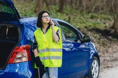 aantrekkelijk meisje die telefonisch dichtbij auto op weg in veiligheidshefboom spreken royalty-vrije stock foto
