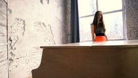 Aantrekkelijk meisje die zich achter de witte grote piano bevinden stock videobeelden