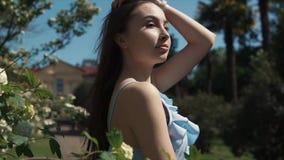 Aantrekkelijk meisje door bloemen in tuin stock video