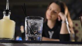 Aantrekkelijk meisje in een goede stemming, die bij de bar, met een glas in haar hand zitten stock video