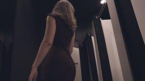 Aantrekkelijk meisje in een manieropslag die op een kleding proberen stock video