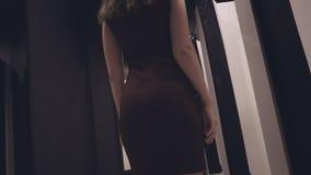 Aantrekkelijk meisje in een manieropslag die op een kleding proberen stock videobeelden