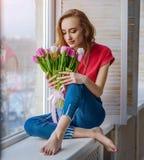 Aantrekkelijk meisje met boeket van tulpen op vensterbank Royalty-vrije Stock Afbeelding