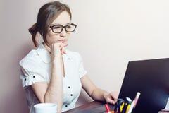 Aantrekkelijk meisje met de glazen die op laptop typen Royalty-vrije Stock Afbeeldingen