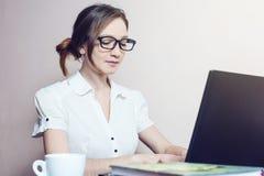 Aantrekkelijk meisje met de glazen die op laptop typen Stock Afbeelding