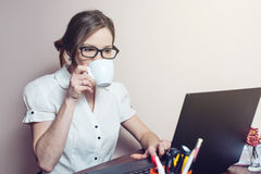 Aantrekkelijk meisje met de glazen die op laptop typen Stock Foto's