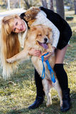 Aantrekkelijk meisje met haar hond die warme kleren dragen Stock Foto's